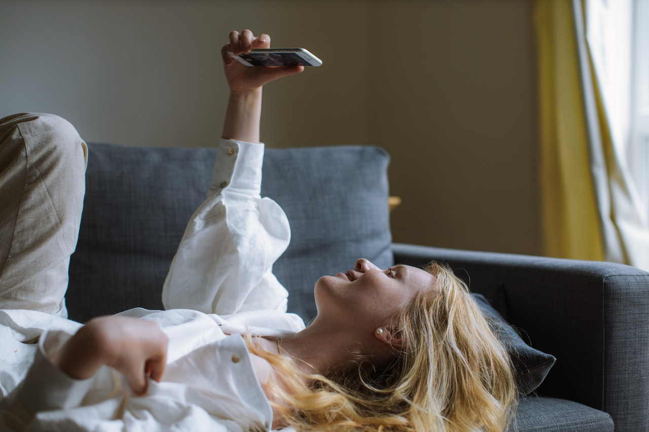 woman laying down while taking video call