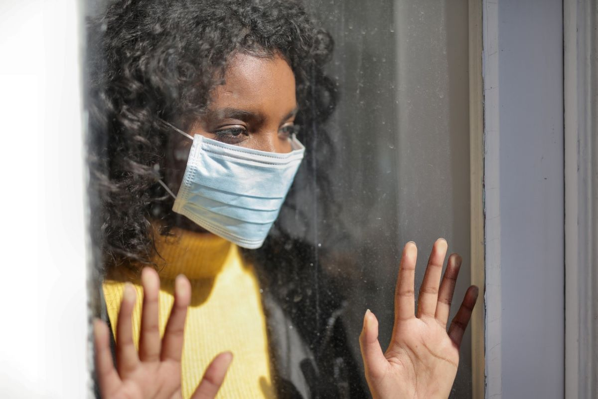 woman looking out the window wearing face mask
