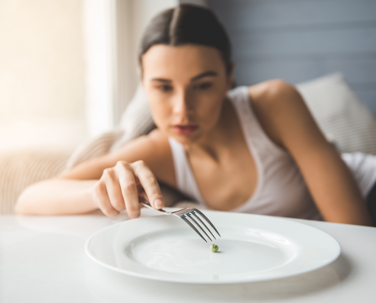 Woman using a fork to eat a pea