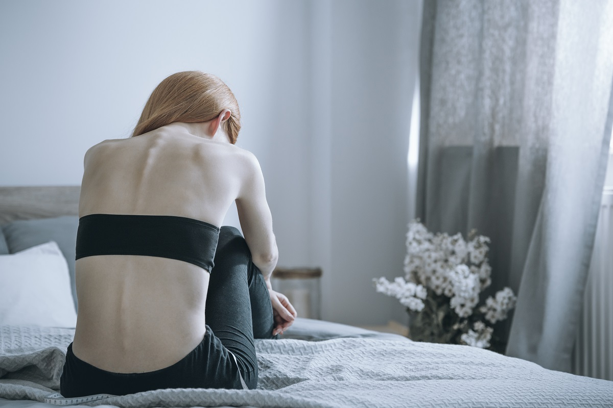 Skinny woman sitting on her bed